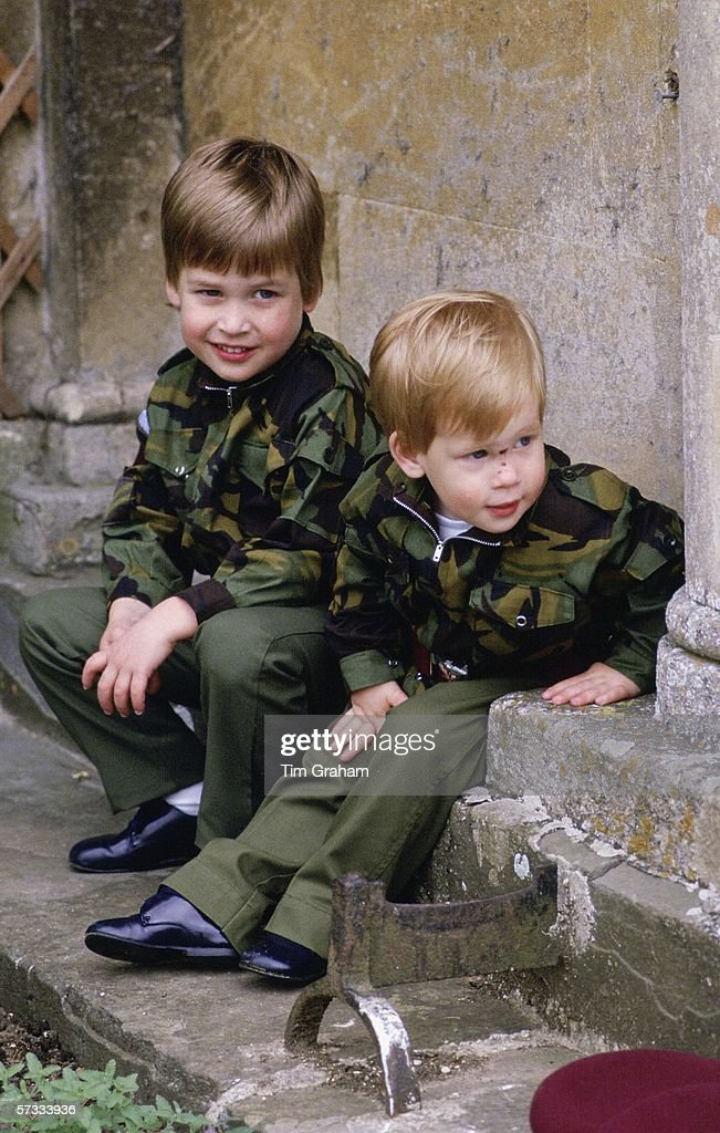 Prince Harry and Prince William sit together on the steps of Highgrove House wearing army uniforms on July 18 1986 in Tetbury England