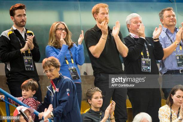 Prince Harry applauds a Canadian World War II veteran before the wheelchair rugby match between the United States and Denmark at the Invictus Games...