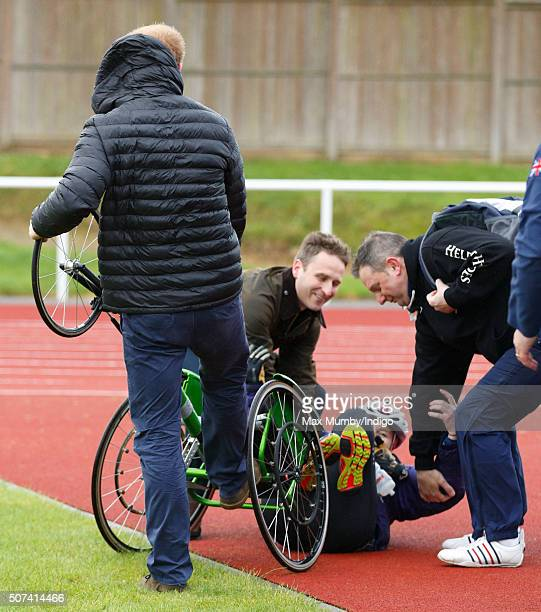 Prince Harry assists wheelchair athlete Anna Pollock after a gust of wind blew over her wheelchair as he attends the UK team trials for the Invictus...