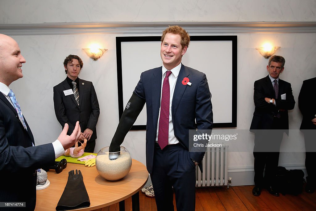 Prince Harry attempts to pick objects out of a bowl filled with rice whist wearing a glove to simulate what it would feel like to pick up objects if he had a brain injury during a visit to Headway, the brain injury association at Bradbury House during an official visit to Nottingham on April 25, 2013 in Nottingham, England.