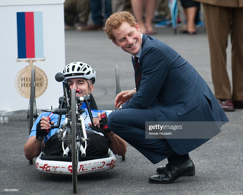 Prince Harry bends to talk to competitors in the the Hero Ride charity race as he visits Help For Heroes Recovery Centre on May 20, 2013 in Tidworth, England.