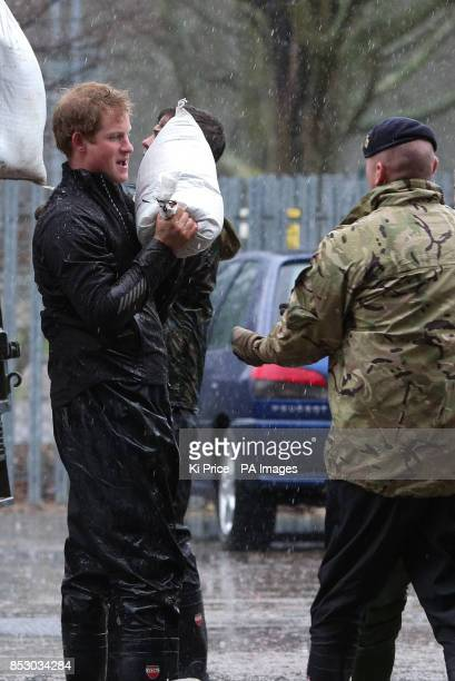 Prince Harry carrying sandbags in Datchet Berkshire as he and his brother the Duke of Cambridge joined colleagues from the armed forces in helping to...