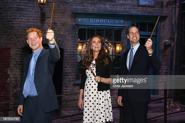 Prince Harry Catherine Duchess of Cambridge and Prince William Duke of Cambridge raise their wands on the set used to depict Diagon Alley in the...