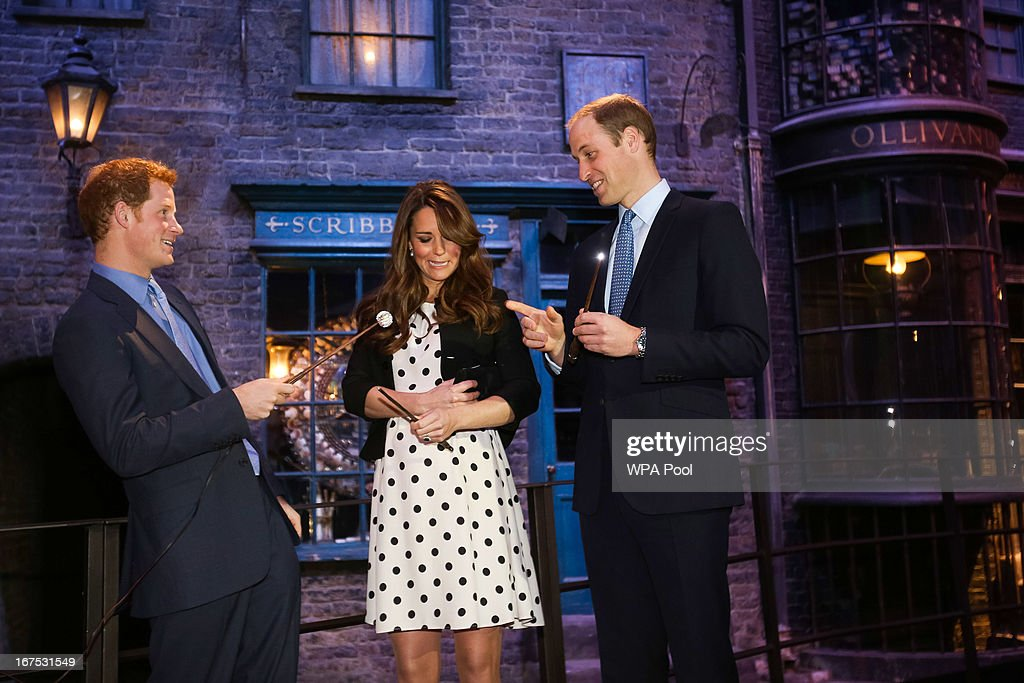 Prince Harry, Catherine, Duchess of Cambridge and Prince William, Duke of Cambridge raise their wands on the set used to depict Diagon Alley in the Harry Potter Films during the Inauguration Of Warner Bros. Studios Leavesden on April 26, 2013 in London, England.