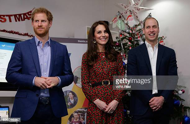 Prince Harry Catherine Duchess of Cambridge and Prince William Duke of Cambridge stand ready to give an award during a visit to a Christmas party for...