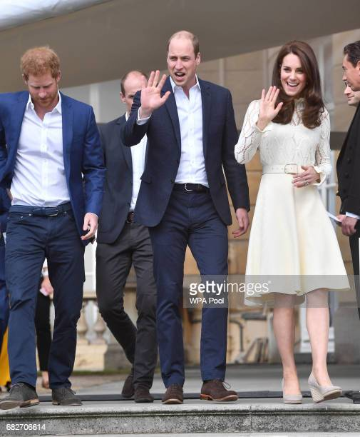 Prince Harry Catherine Duchess of Cambridge and Prince William Duke of Cambridge laugh host a tea party in the grounds of Buckingham Palace to honour...