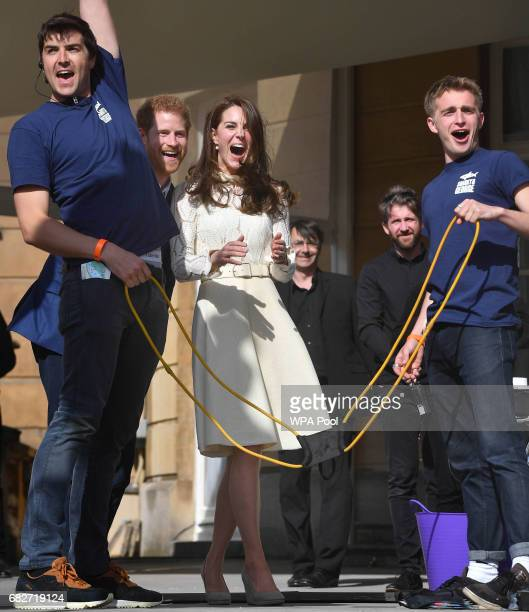 Prince Harry Catherine Duchess of Cambridge and Prince William Duke of Cambridge laugh as they host a tea party in the grounds of Buckingham Palace...
