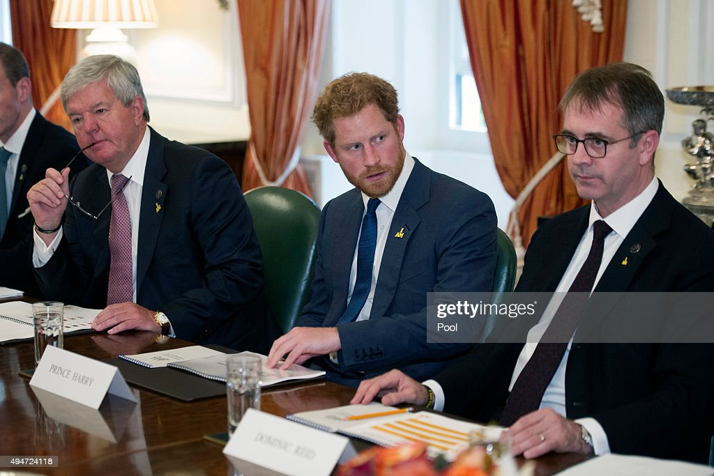 Prince Harry, center right, is flanked by Invictus Chairman Sir Keith Mills, left, and Managing Director Domenic Reid, as he attends an Invictus Board meeting at the British Ambassador's Residence on October 28, 2015 in Washington DC.