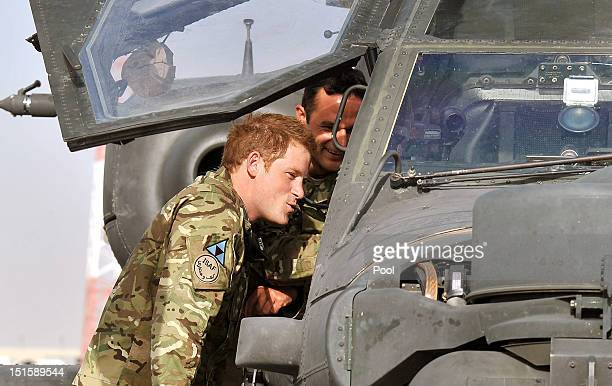Prince Harry climbs up to examine the cockpit of an Apache helicopter with a member of his squadron on September 7 2012 at Camp Bastion Afghanistan...