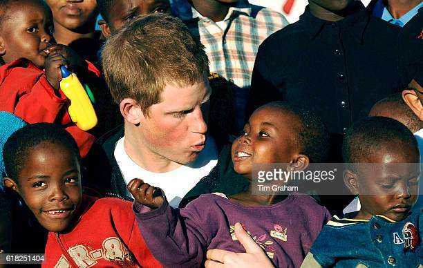 Prince Harry cuddles children Mutsu and Lintle at Mants'ase children's home in Lesotho in southern Africa and launches his charity called 'Sentebale'...