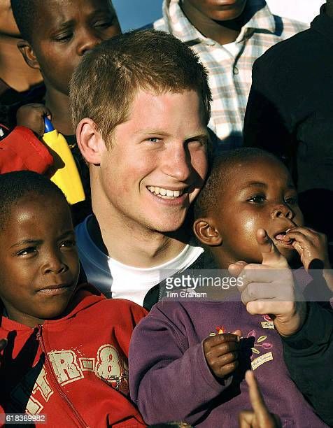 APRIL 28 2006*** Prince Harry cuddles children Mutsu and Lintle in the grounds of the Mants'ase children's home while on a return visit to Lesotho in...