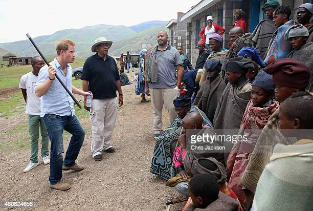 Prince Harry dances in front of herd boys with Prince Seeiso of Lesotho during a visit to a herd boy night school constructed by Sentebale on...