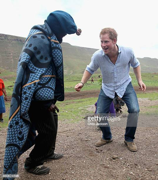 Prince Harry dances with the village chief during a visit to a herd boy night school constructed by Sentebale on December 8 2014 in Maseru Lesotho...