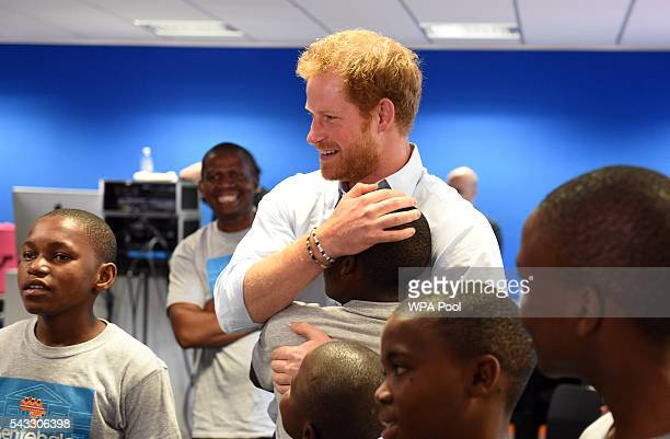 Prince Harry embraces 16 yearold Relebohile 'Mutsu' Potsane after watching members of the Basotho Youth Choir during their rehearsals at the Brit...