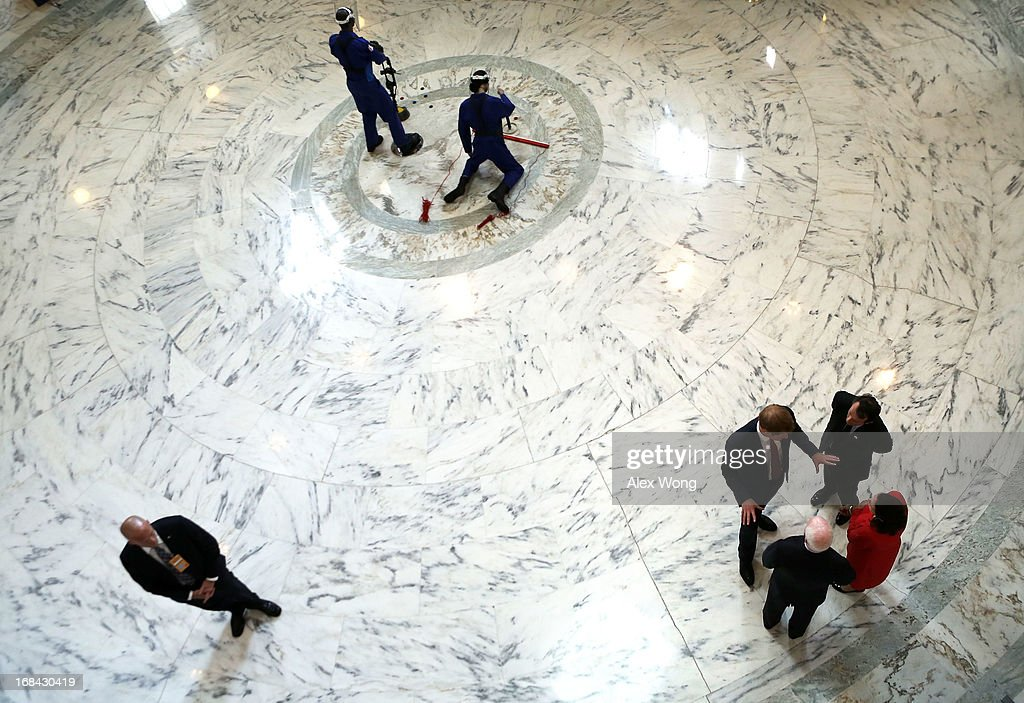 Prince Harry (L), escorted by HALO Trust Director Guy Willoughby (3rd L) and his wife Fiona Willoughby (R), and U.S. Senator John McCain (R-AZ) (2nd L), tours an exhibit on landmines and unexploded ordnances inside the Rotunda of Russell Senate Office Building on Capitol Hill during the first day of his visit to the United States May 9, 2013 in Washington, DC. HRH will be undertaking engagements on behalf of charities with which the Prince is closely associated on behalf also of HM Government, with a central theme of supporting injured service personnel from the UK and US forces.