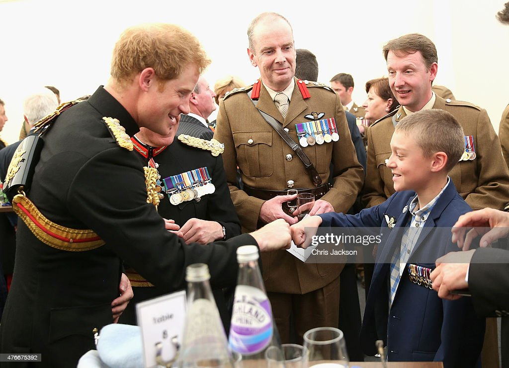 Prince Harry fist bumps Jack Faulkner as he meets familes of those who lost their lives in Afghanistan after the unveiling of the Bastion Memorial at The National Memorial Arboretum on June 11, 2015 in Stafford, England.