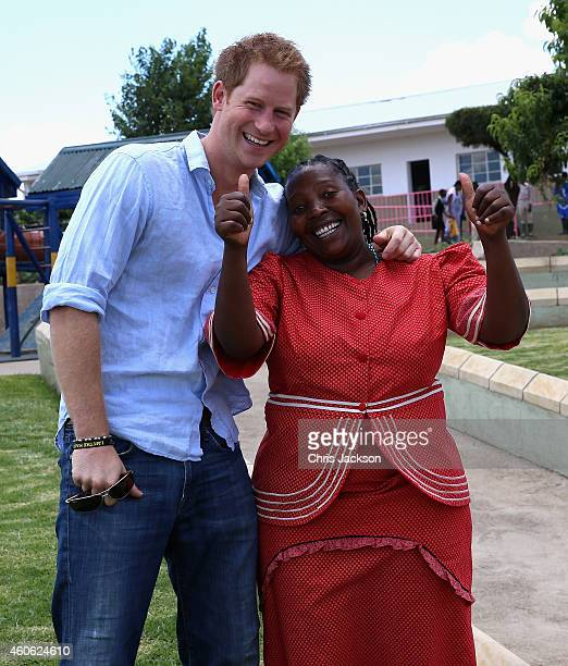 Prince Harry gives a thumbs up with Head Teacher of the Thuso Centre Mamonuku Mofilikoane in front of a playground and path he helped build in 2008...