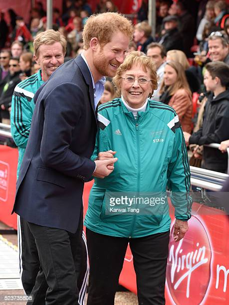 Prince Harry gives Sylvia Disley a helping hand after she fell during the medal presentation the Virgin London Marathon 2016 on April 24 2016 in...