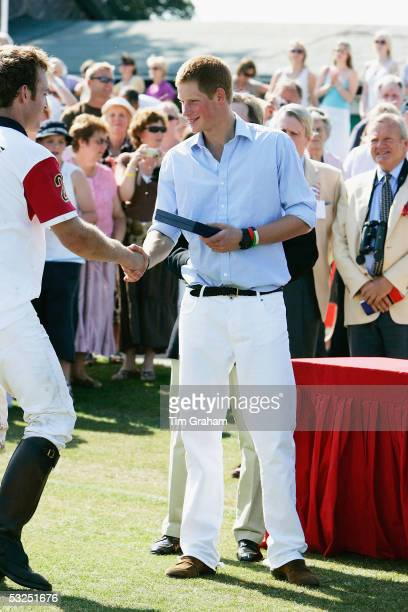 Prince Harry hands out prizes at Cirencester Park after playing polo for the Emlor team against the Corramore team at Cirencester Park on July 17...