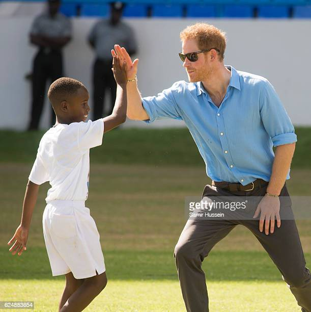 Prince Harry high fives a boy at a Youth Sports Festival at the Sir Vivian Richards Stadium on the second day of an official visit on November 21...