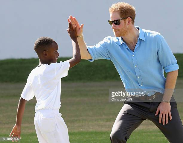 Prince Harry high fives a young cricket player as he attends a youth sports festival at Sir Vivian Richards Stadium showcasing Antigua and Barbuda's...