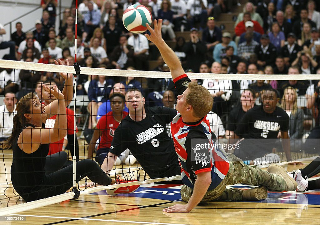 HRH Prince Harry hits the ball to former U.S. Olympic beach volleyball great Misty May-Treanor (L) as they play sitting volleyball with the UK team at a visit to the Warrior Games Opening at the U.S. Olympic Training Center on May 11, 2013 in Colorado Springs, Colorado. HRH will be undertaking engagements on behalf of charities with which the Prince is closely associated on behalf also of HM Government, with a central theme of supporting injured service personnel from the UK and US forces.