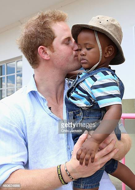 Prince Harry holds a young child during a visit to Thuso Centre for children living with multiple disabilities on December 7 2014 in ButeBute Lesotho...