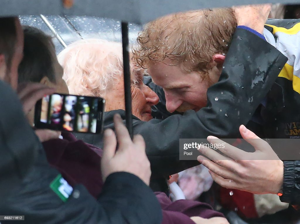 Prince Harry hugs 97-year-old Daphne Dunne, who he had met on an earlier visit to Sydney, during an event where he met members of the public in the pouring rain at The Rocks on June 7, 2017 in Sydney, Australia. Prince Harry is on a two-day visit to Sydney for the launch of the Invictus Games Sydney 2018. The fourth Invictus Games will be held in Sydney from 20th to 27th October, 2018 and will include over 500 competitors from 17 nations competing in 10 adaptive sports events.