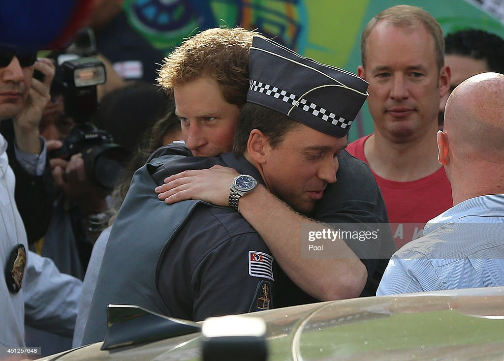 Prince Harry hugs a policeman as he visits the Open Arms project which helps reduce crime and drug abuse in 'Cracolandia', an extremely deprived area of Sao Paulo with a high concentration of crack addicts on June 26, 2014 in Sao Paulo Brazil. Crack in Sao Paulo costs just 80 UK pence for a rock of the drug. Prince Harry is on a four day tour of Brazil that will be followed by two days in Chile.