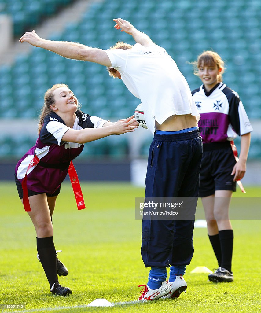 Prince Harry (R), in his role as Patron of the Rugby Football Union All Schools Programme, takes part in a rugby coaching session at Twickenham Stadium on October 17, 2013 in London, England.