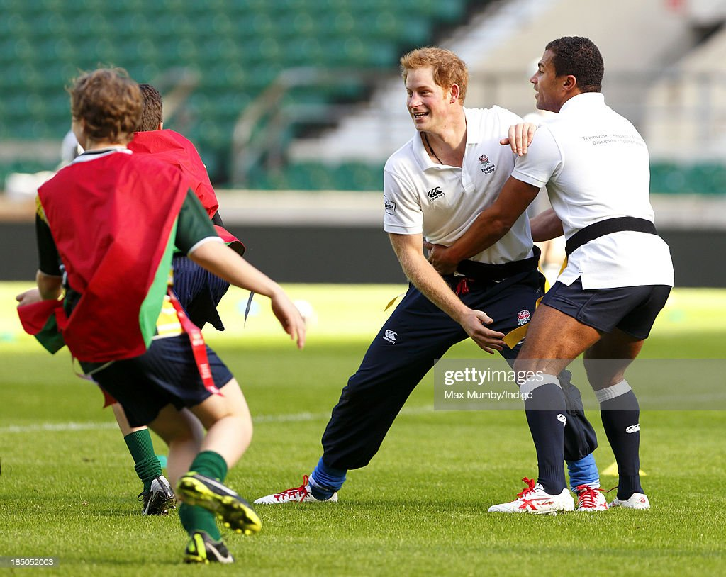 Prince Harry, in his role as Patron of the Rugby Football Union All Schools Programme and former England International Jason Robinson tussle as they take part in a rugby coaching session at Twickenham Stadium on October 17, 2013 in London, England.