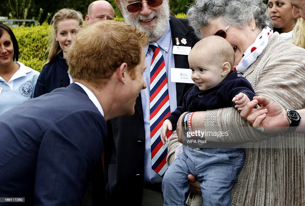 Prince Harry interacts with a young child during his visit to Tedworth House to officially open the charity's Tedworth House recovery centre on May 20, 2013 in Tidworth, England. During their visit the two Royal Princes met with wounded veterans, serving personnel, and their families. Tedworth House in Wiltshire is one of four new units in England which will offer respite care and rehabilitation to injured and sick service personnel, veterans and their families.