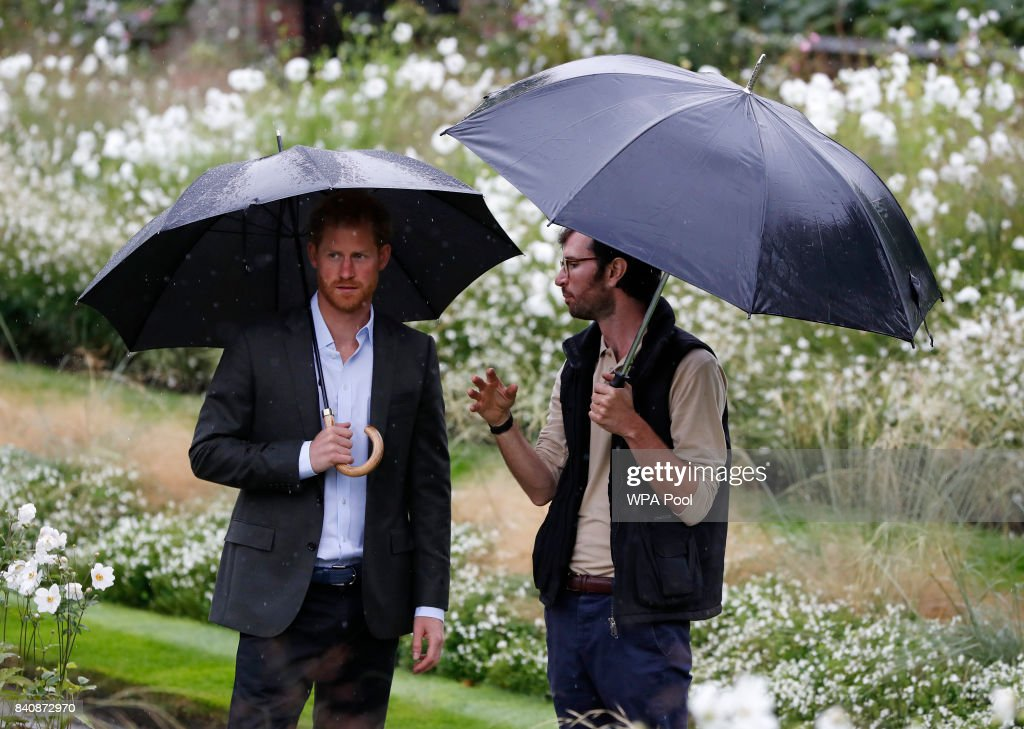 Prince Harry (L) is escorted during a visit to The Sunken Garden at Kensington Palace on August 30, 2017 in London, England. The garden has been transformed into a White Garden dedicated in the memory of Princess Diana, mother of The Duke of Cambridge and Prince Harry.