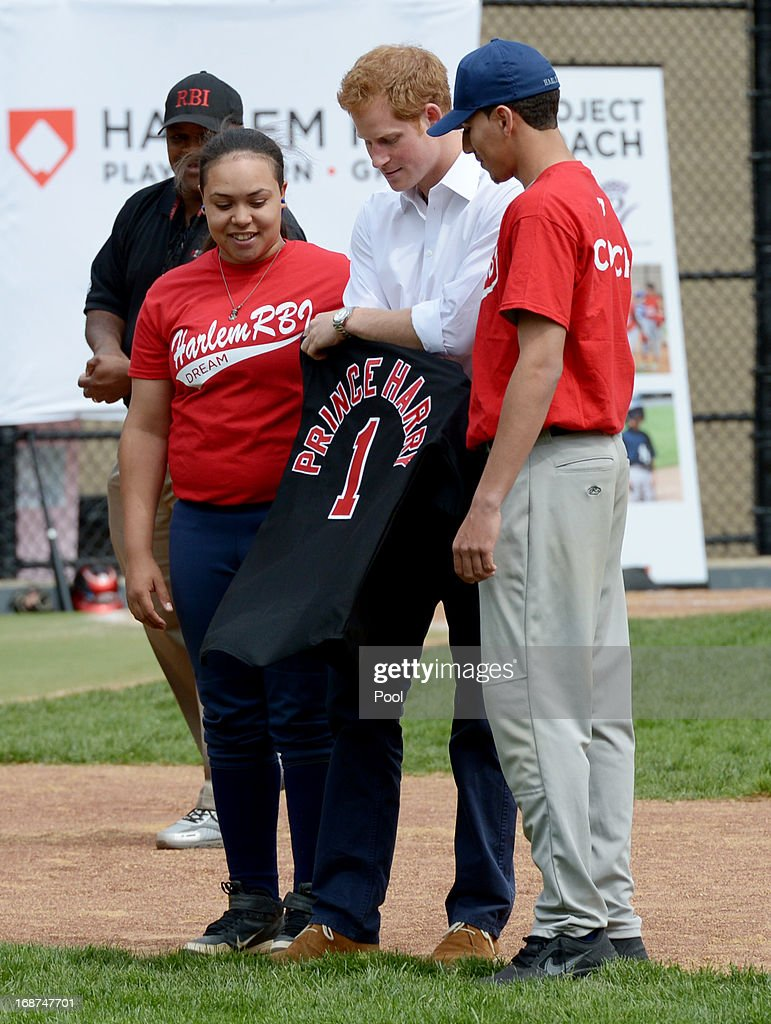 Prince Harry (C) is given a baseball jersey while participating in a baseball clinic during the launch of a new partnership between the Royal Foundation of the Duke and Duchess of Cambridge and Harlem RBI, a local community organization May 14, 2013 in the Harlem neighborhood of New York City. HRH will be undertaking engagements on behalf of charities with which the Prince is closely associated on behalf also of HM Government, with a central theme of supporting injured service personnel from the UK and US forces.