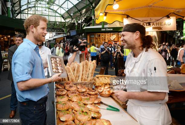Prince Harry is given a book by the Bread Ahead stand as he tours stalls during a visit to Borough Market which has opened yesterday for the first...