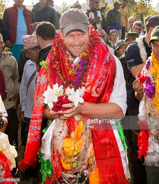 Prince Harry is given garlands and flowers as he visits Gauda Secondary School an earthquakedamaged school being reconstructed with assistance from...