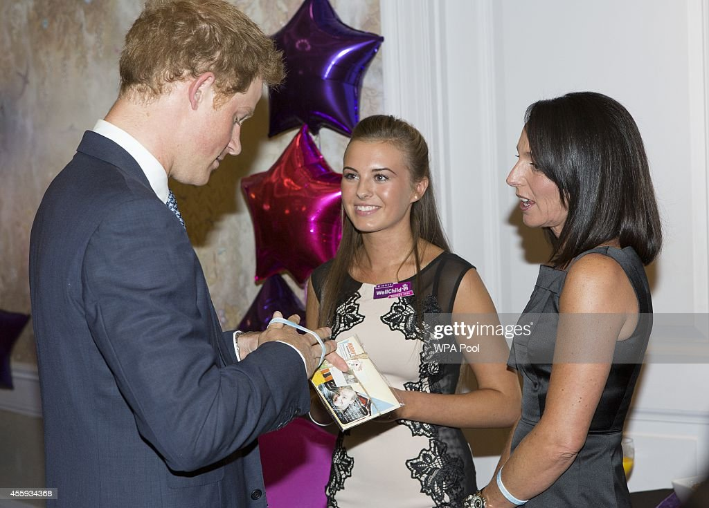 Prince Harry is presented with a charity wrist band by Rosie Flory (15) , Most caring young person award award winner, as he meets her and her mother Michelle during the WellChild awards at the London Hilton on September 22, 2014 in London, England.