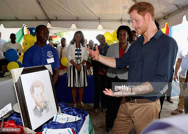 Prince Harry is presented with a portrait as he visits mangrove restoration projects on Grand Anse Beach ahead of visiting the coral reef on the...