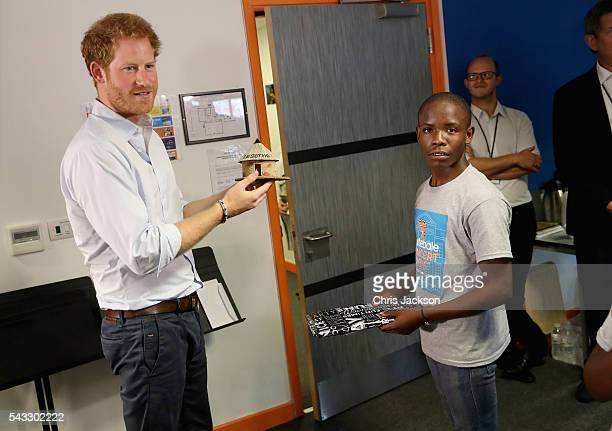 Prince Harry is presented with gifts by 16 yearold Relebohile 'Mutsu' Potsane who is singing as part of the Basotho Youth Choir made up of six boys...