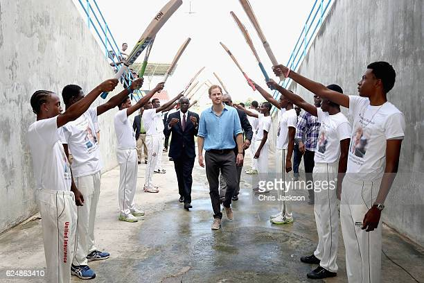 Prince Harry is saluted by young cricket players as he attends a youth sports festival at Sir Vivian Richards Stadium showcasing Antigua and...