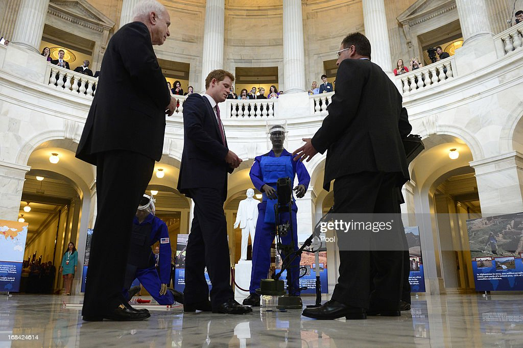 Prince Harry (2-L) is shown a ground penetrating radar, a tool used for detecting land mines, during tour of a HALO Trust photo exhibit on landmines and unexploded ordinances, with Republican Senator from Arizona John McCain (L) and HALO Trust Weapons and Ammunition Disposal Desk Officer Richard Boulter (R), on Capitol Hill on May 9, 2013 in Washington, DC. HRH will be undertaking engagements on behalf of charities with which the Prince is closely associated on behalf also of HM Government, with a central theme of supporting injured service personnel from the UK and US forces.