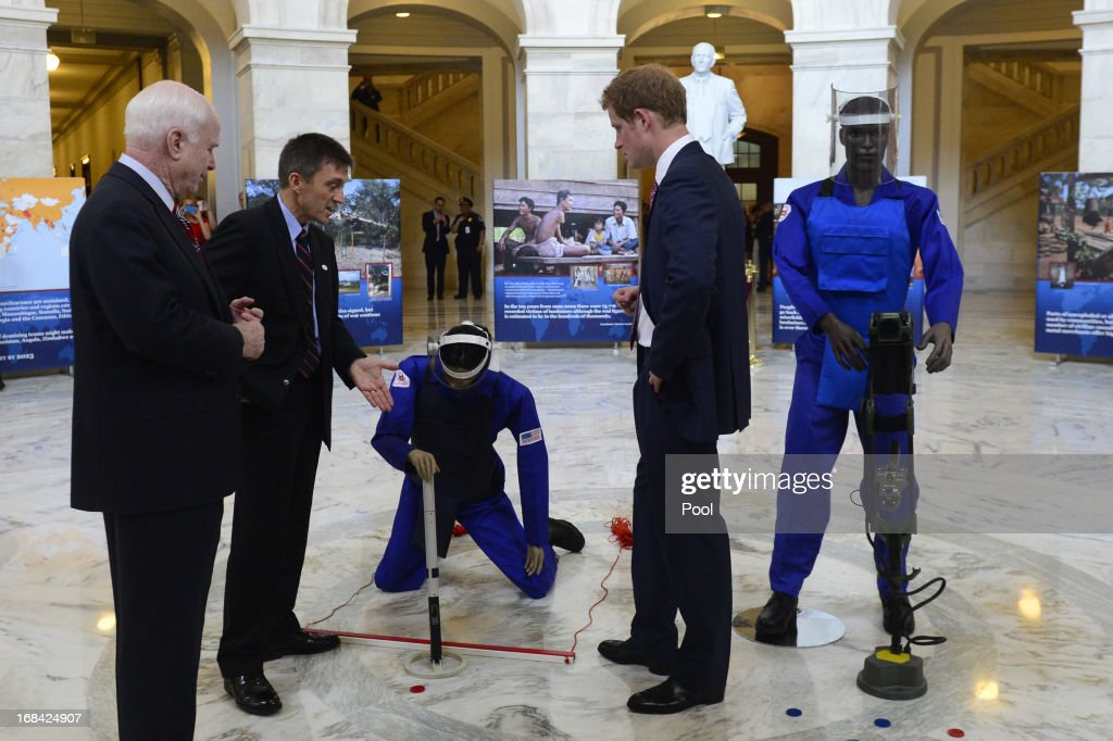 Prince Harry (R) is shown equipment used for detecting land mines during a tour of a HALO Trust photo exhibit on landmines and unexploded ordinances, with Republican Senator from Arizona <a gi-track='captionPersonalityLinkClicked' href=/galleries/search?phrase=John+McCain&family=editorial&specificpeople=125177 ng-click='$event.stopPropagation()'>John McCain</a> (L) and HALO Trust Afghanistan Desk Officer Tim Porter (2-L), on Capitol Hill on May 9, 2013 in Washington, DC. HRH will be undertaking engagements on behalf of charities with which the Prince is closely associated on behalf also of HM Government, with a central theme of supporting injured service personnel from the UK and US forces.