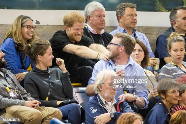 Prince Harry jokes with another spectator at the wheelchair rugby match between the United States and Denmark at the Invictus Games in Toronto...