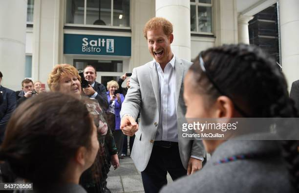 Prince Harry jokes with school children that they should be at school as he meets members of the public as he toured St Anne's Square as part of his...