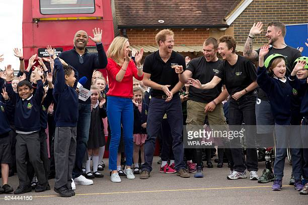 Prince Harry laughs as one of the school pupils dances with presenters Darren Campbell and Di Dougherty and competitors Scott Meenagh Mary Wilson and...