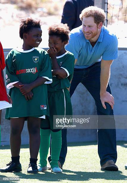 Prince Harry laughs with young girls during a visit to a Football for Hope session with Grassroots Soccer in Khayelitsha on November 30 2015 in Cape...