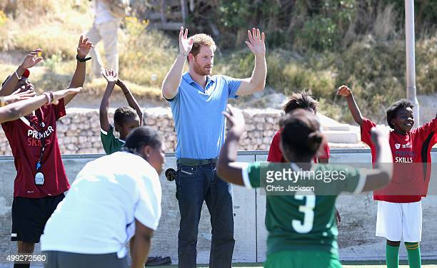 Prince Harry lifts his hands during a visit to a Football for Hope session with Grassroots Soccer in Khayelitsha on November 30 2015 in Cape Town...