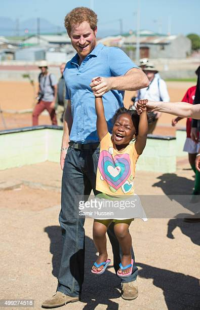 Prince Harry lifts up fouryearold Sinentlantla Jacobs during a visit to Football For Hope Centre in Khayelistsha during an official visit to Africa...