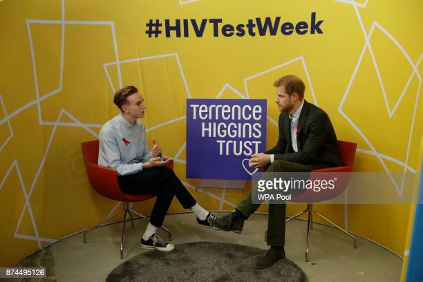 Prince Harry listens listens as Andrew Bates tells his story of his life after being diagnosed with HIV in 2015 during his visit to the opening of...