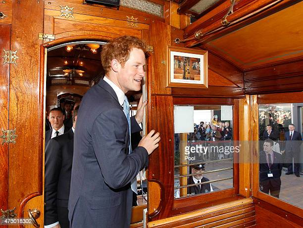 Prince Harry looks at a picture of his grandmother Queen Elizabeth II on the same tram shot in 1995 whilst on a ride on the historic Christchurch...